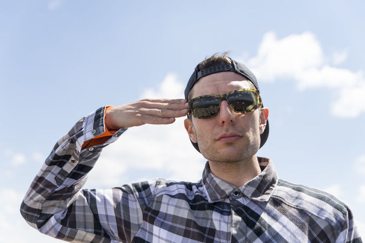 Man saluting against sky