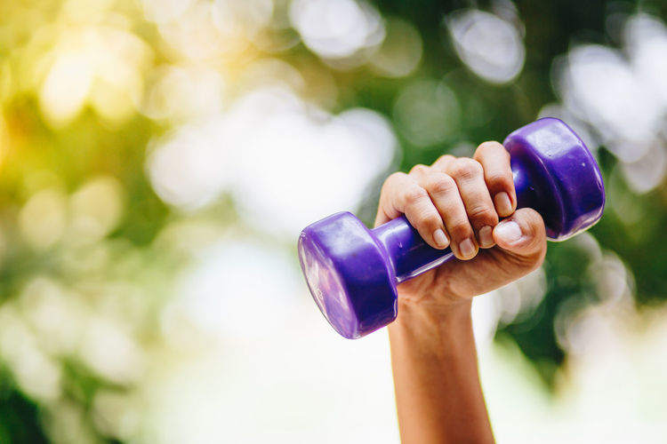 Adult Body Part Close-up Day Dumbbell Finger Focus On Foreground Hand Healthy Lifestyle Holding Human Arm Human Body Part Human Hand Human Limb Leisure Activity Lifestyles Nature One Person Outdoors Purple Real People Vitality Weight Training  Weights