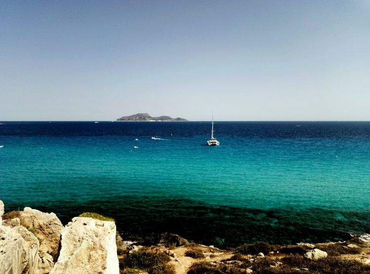 Boat Horizon Over Water Tranquil Scene Beach Sea Tranquillity Catamaranboat Bushes Rocks Blue Sea And Clear Water Island