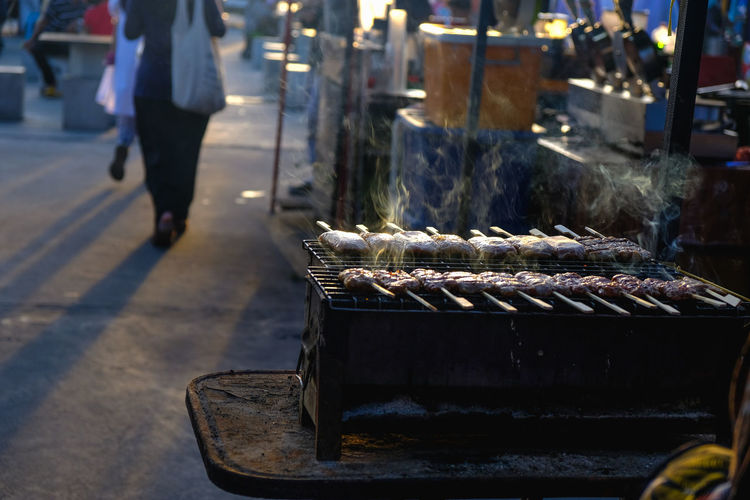 Low section of person on barbecue grill at market