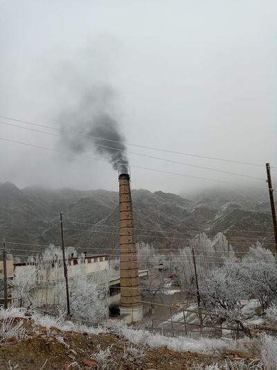 Smoke emitting from chimney against sky during winter