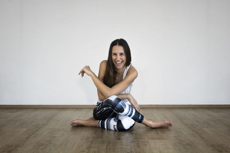 Portrait of smiling young woman sitting on hardwood floor against wall