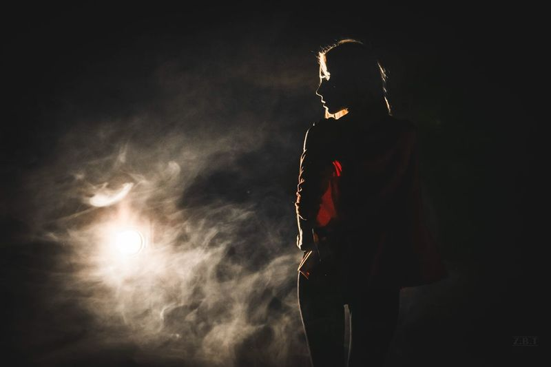 Rear view of silhouette woman standing against sky at night