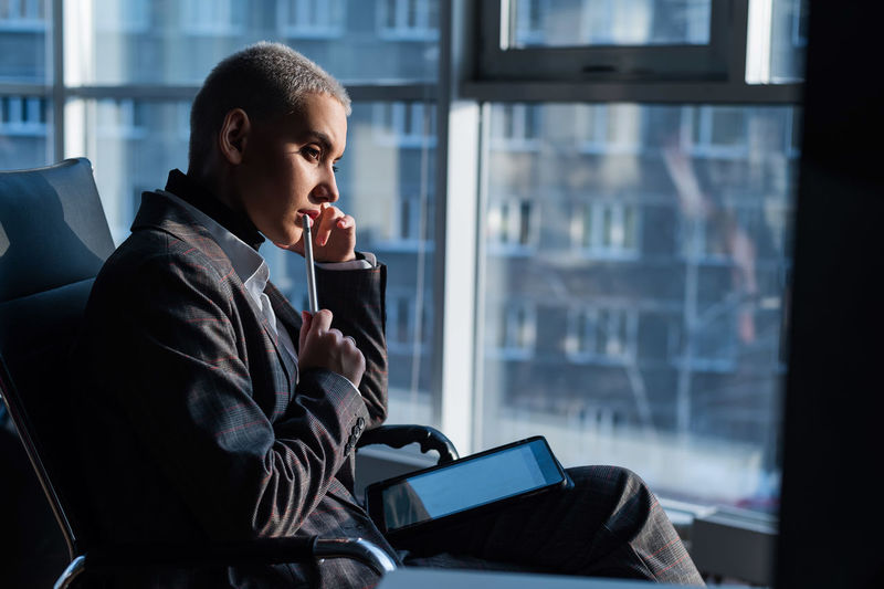 Young man using mobile phone while sitting on window