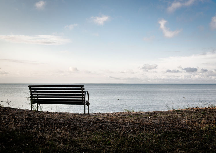 Empty bench on shore at beach
