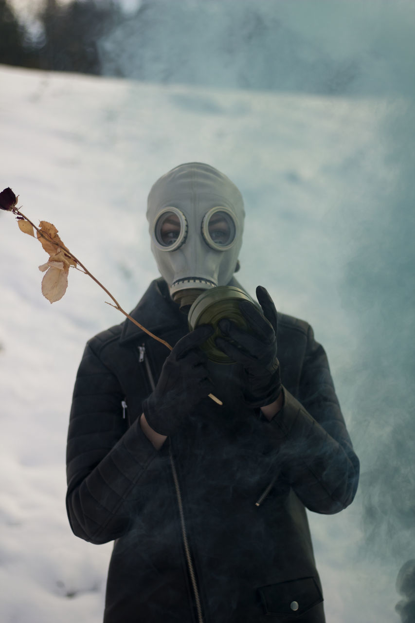 Person In Gas Mask Holding Twig During Winter