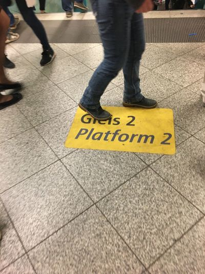 Gleis 2 Sign Body Part Bvg Flooring Indoors  Information Low Section People Platform Subway Subway Station Text Tiled Floor Walking Western Script Yellow