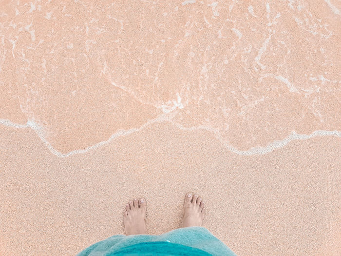 Low section of person standing at beach