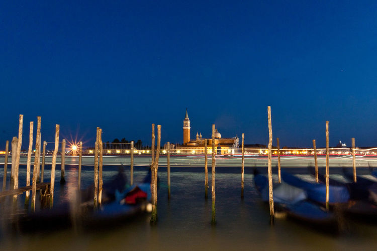 Gondolas moored on grand canal against st marks square at night