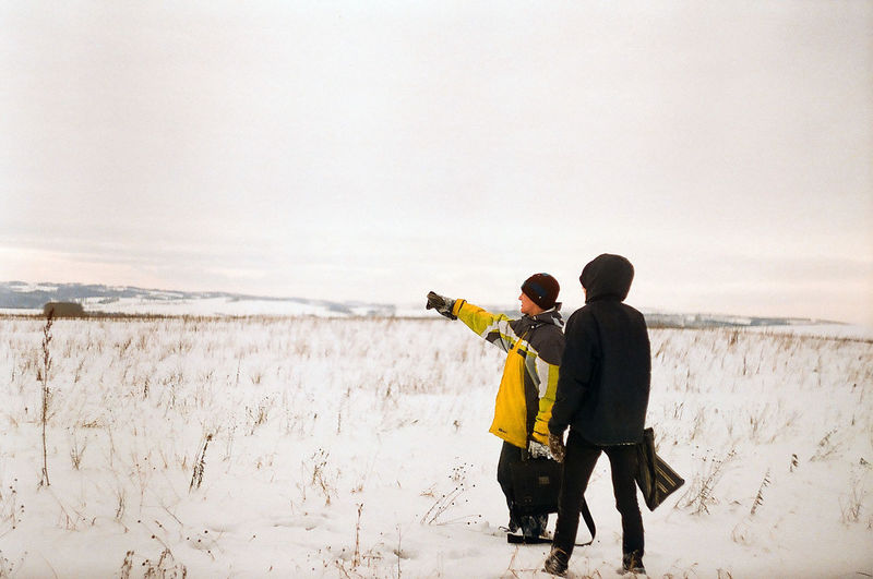 Friends Standing On Snow Covered Field Against Sky