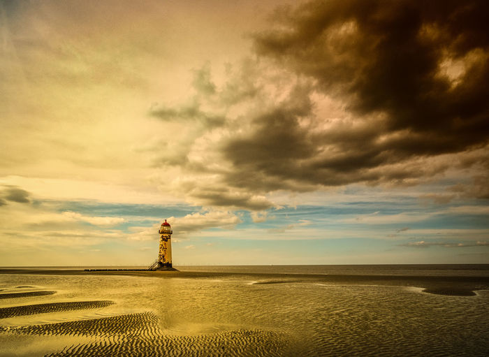 Point Of Ayr Lighthouse At Talacre Beach Against Cloudy Sky During Sunset