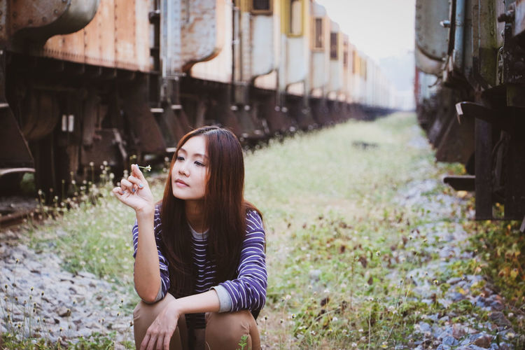 Beautiful young woman holding flower while sitting amidst trains