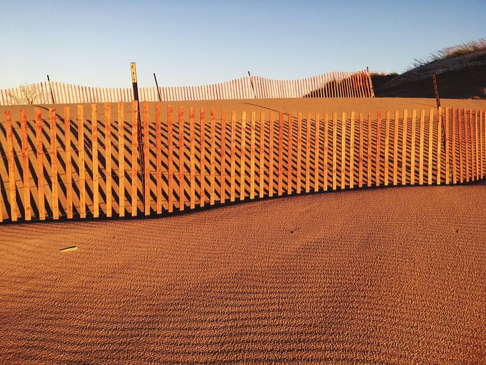 Outdoors No People Nature Day Fence Sand Sand Dune Snow Fence Remote Landscape Arid Climate Orange Beauty In Nature Sunset Travel Destination Natural Pattern Sand Waves Idyllic Horizon Over Land Michigan