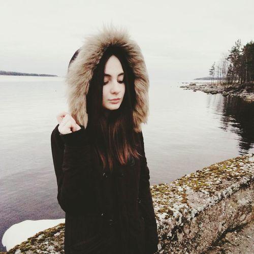 Beautiful Young Woman In Fur Coat Standing At Lakeshore