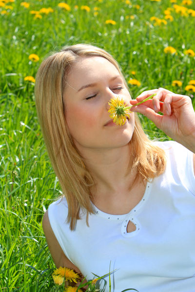 Happy young woman enjoying spring time Beautiful Happy Nature Woman Beauty Blond Hair Close-up Flower Flowers Girl Leisure Leisure Activity Lifestyles Meadow Nature One Person Outdoors People Portrait Pretty Smelling Smells Spring Time Springtime Young Adult