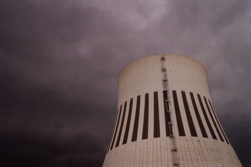 Low angle view of cooling tower against cloudy sky