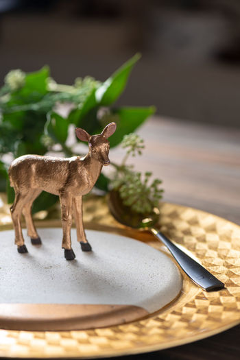 Close-up of deer figurine in plate on table