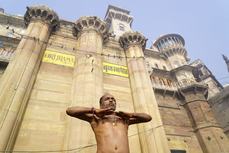 Low angle view of man meditating against historic building