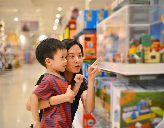 Boy With Mother Looking At Toy In Shopping Mall