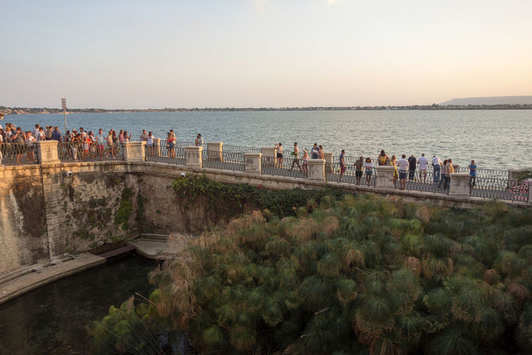 Rear View Of People Overlooking Calm Sea