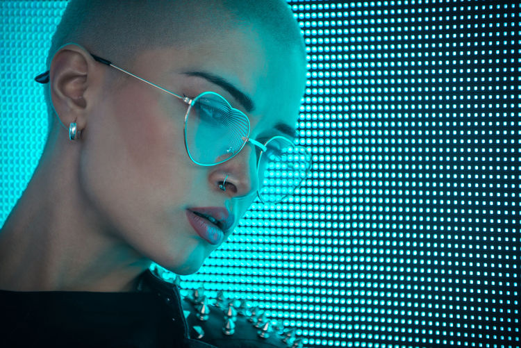 Close-up of young woman with shaved head standing against abstract backgrounds