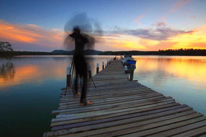 Beauty In Nature Cloud - Sky Lake Leisure Activity Lifestyles Men Nature Orange Color Outdoors Pier Real People Reflection Scenics - Nature Sky Standing Sunset Tranquil Scene Tranquility Water Wood - Material