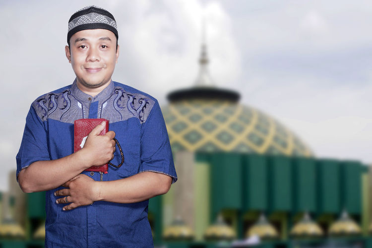 Portrait Smiling asian muslim man on blur mosque background