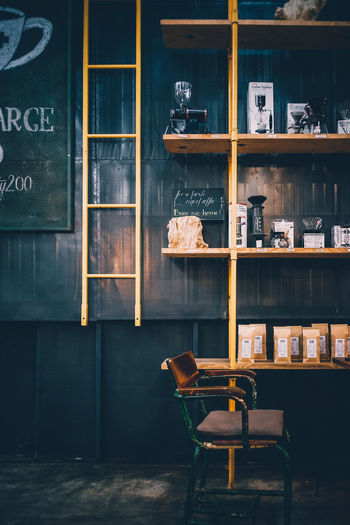 Empty Chair By Shelf At Cafe