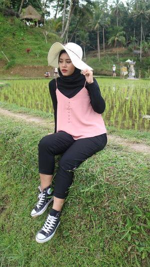Beautiful young woman sitting on grassy field