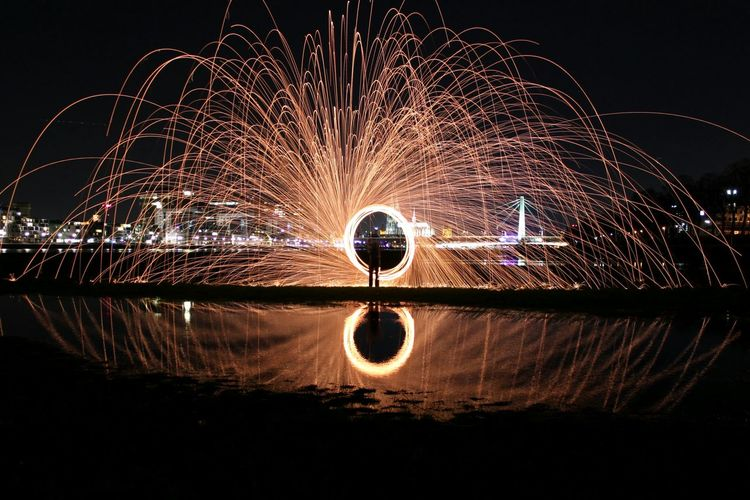Person Making Light Painting With Reflection In Lake Against Sky