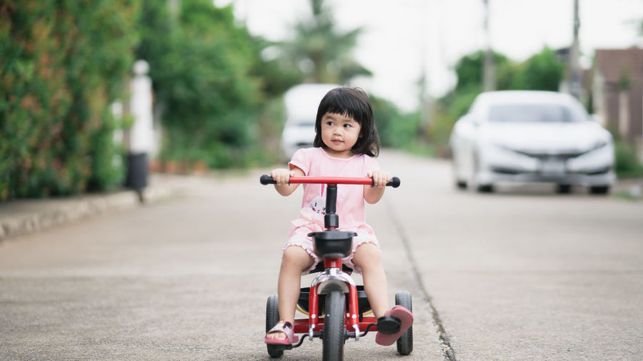 Portrait of cute boy riding toy car on road in city