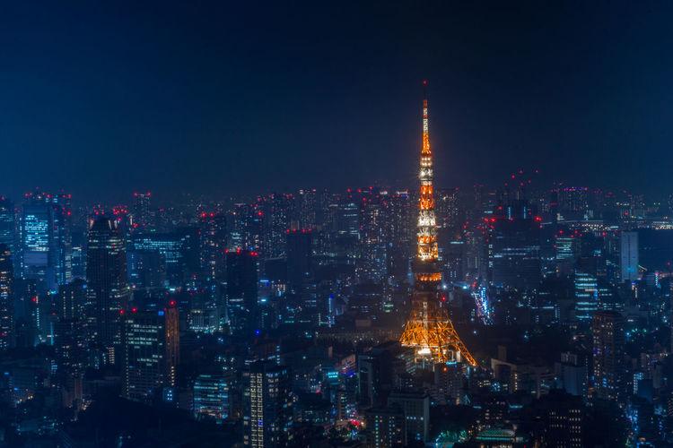 Tokyo tower against tokyo skyline at night, illuminated cityscape