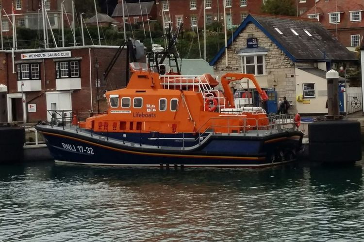 RNLI Lifeboat Moored up to the Dock . Featuring Water Business Finance And Industry Nautical Vessel No People Harbor Industry Commercial Dock Outdoors Day Building Exterior City Architecture Cityscape Blue Orange Boat Life Saving Charity Rescue Service Rescue Waterfront