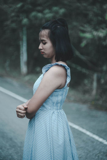 Side view of young woman standing on road