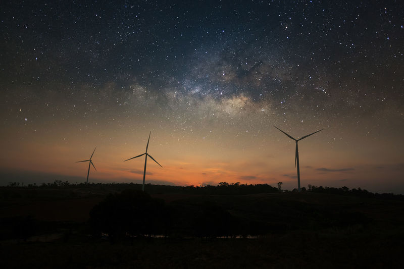 Silhouette wind turbines on field against sky at night