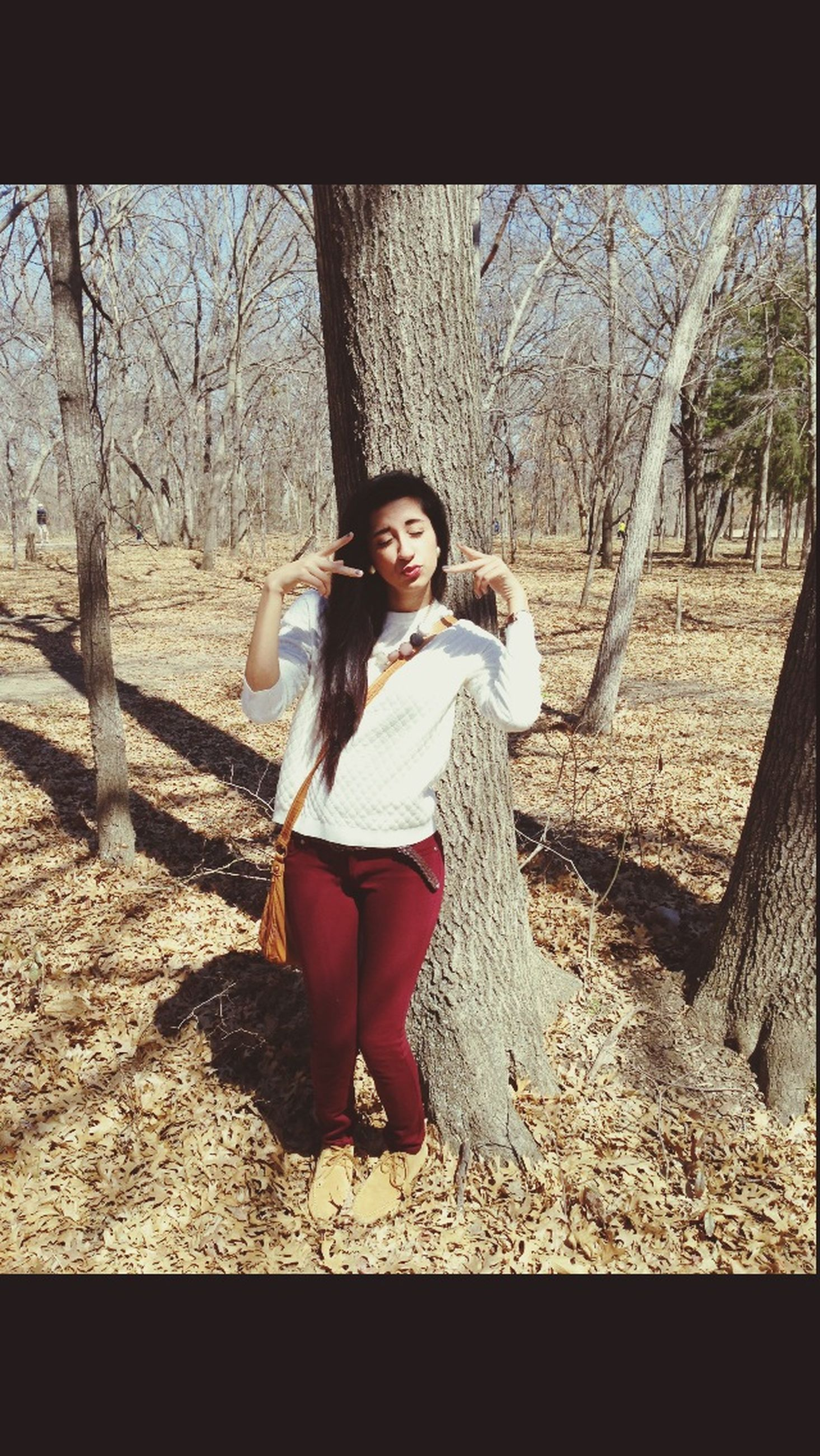 person, looking at camera, portrait, full length, casual clothing, tree, lifestyles, leisure activity, young adult, front view, smiling, childhood, happiness, young women, elementary age, sitting, standing, tree trunk