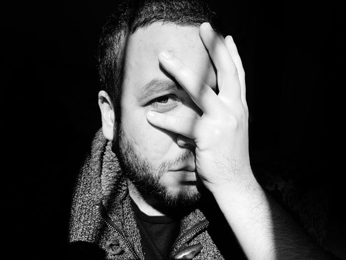 Close-Up Portrait Of Man Covering Face With Hands In Darkroom