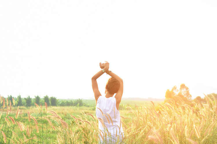 Woman standing in wheat field against clear sky