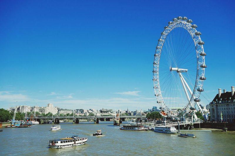 London Eye By Thames River Against Blue Sky