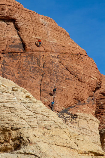 Low angle view of man climbing on rock against sky. red rock canyon, nevada