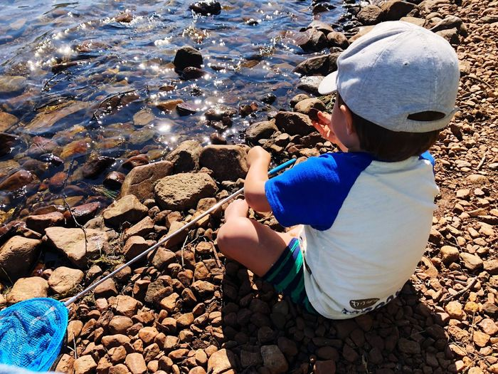 High angle view of child on rock at beach