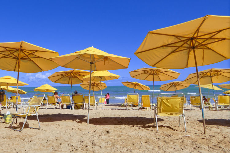 Umbrellas on beach against clear blue sky