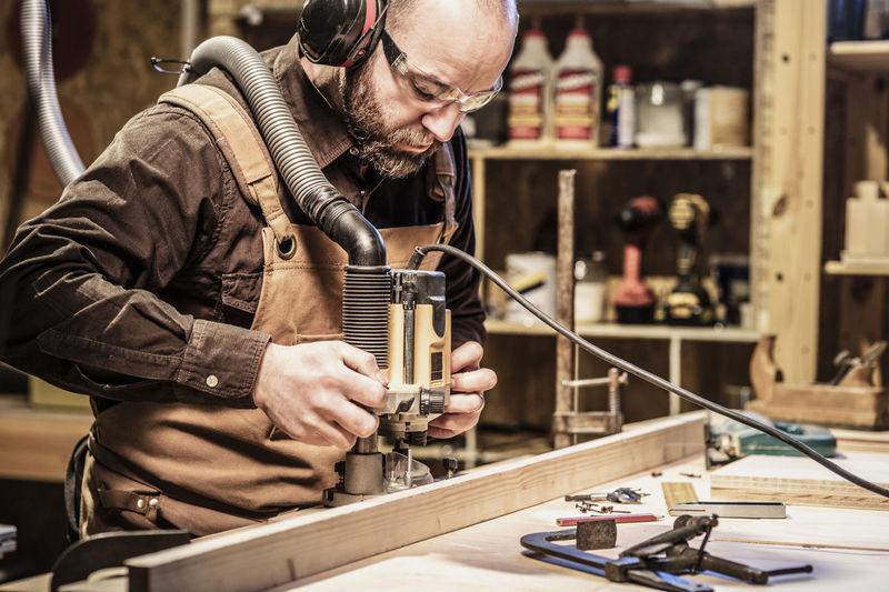 Man Working On Wood At Workshop