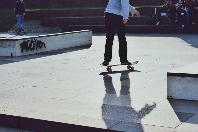 Low Section Of Man Skateboarding On Tiled Floor