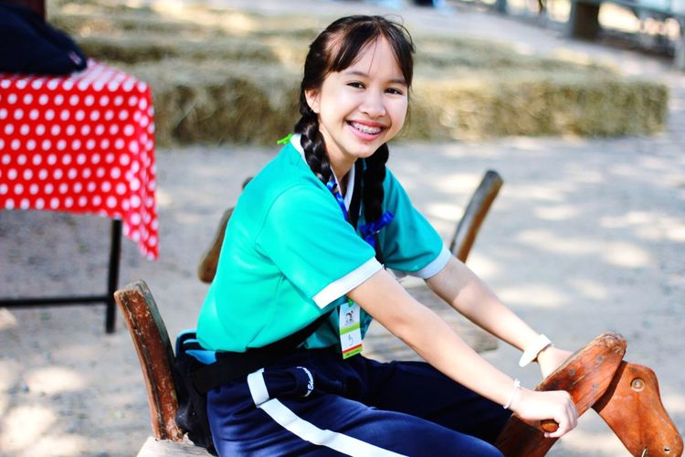 Portrait Of Smiling Woman Sitting On Outdoor Play Equipment At Playground