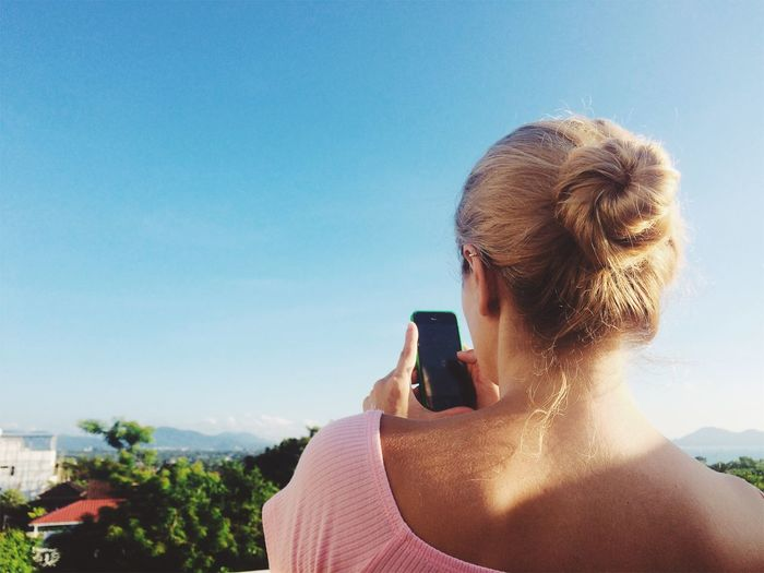 Woman Using Mobile Phone Against Clear Blue Sky