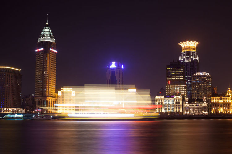 Blurred Motion Of Passenger Ship In River By Illuminated Cityscape At Night