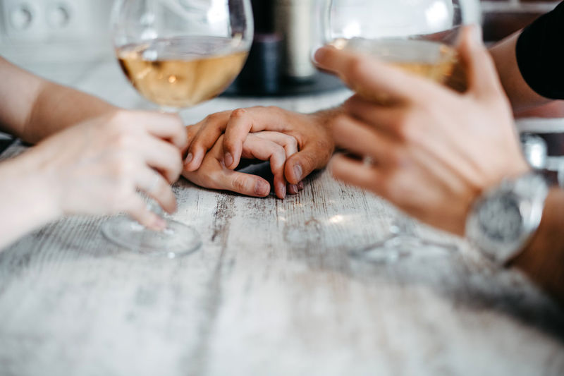 Sweet and romantic dinner. holding hands. two glasses of white wine. lovely couple. relationships