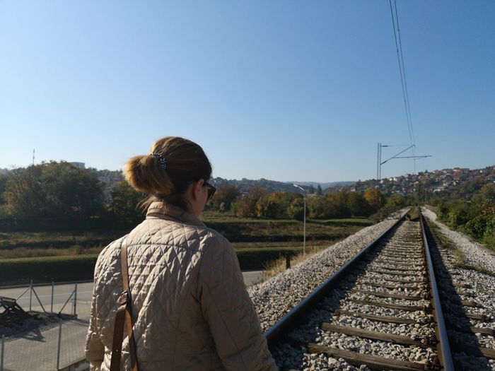 Rear view of man standing on railroad track against clear sky