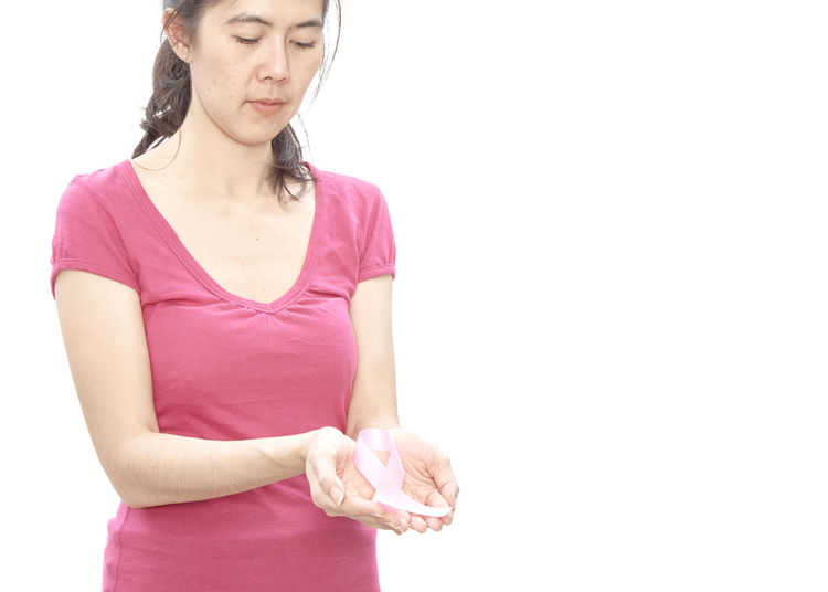 Woman holding pink breast cancer awareness ribbon against white background